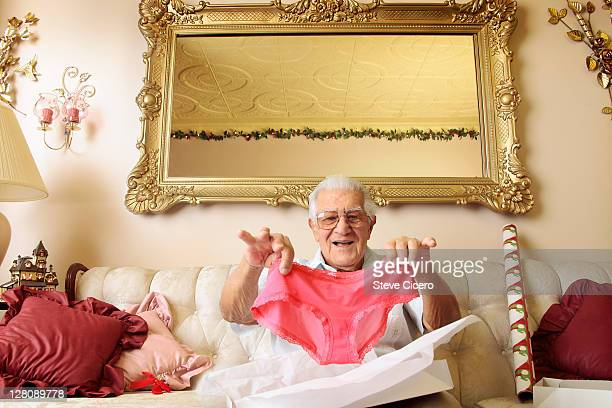 Senior man holding up pink panties
