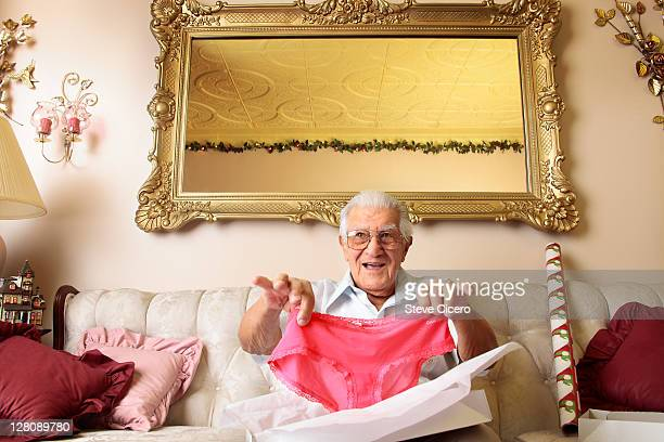 Senior man holding up pink panties