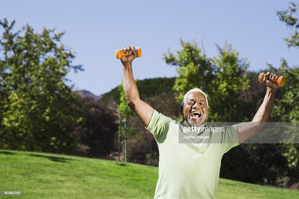 Senior man holding weights with arms outstretched : Stock Photo