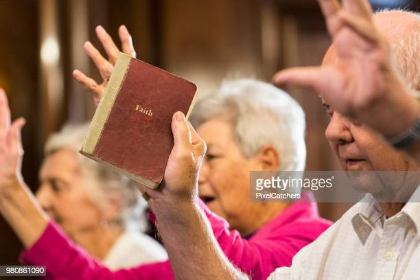 senior man holds prayer book up as the congregation sings in praise - congregation stock pictures, royalty-free photos & images