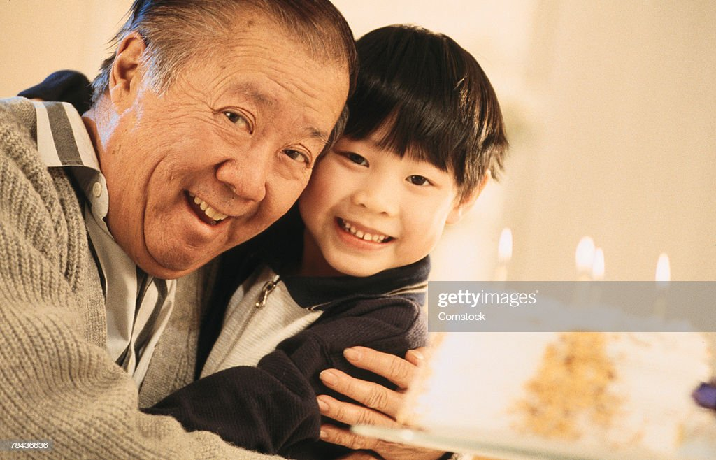 Senior man hugging grandson with birthday cake : Stockfoto