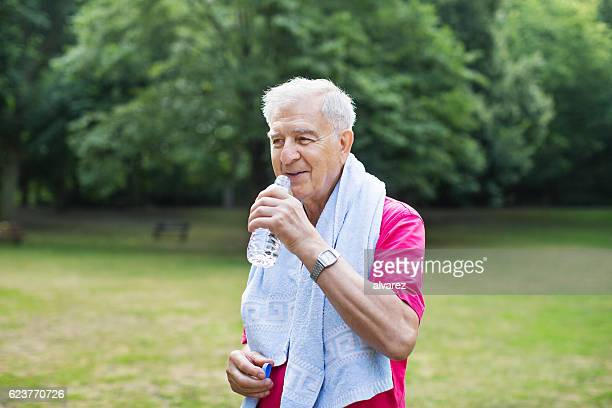 Senior man hydrates after workout in park
