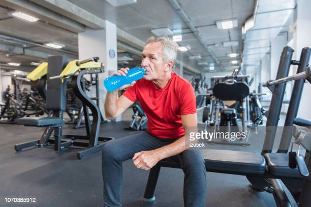 senior man hydrating after workout at rehab gym - izusek stock pictures, royalty-free photos & images