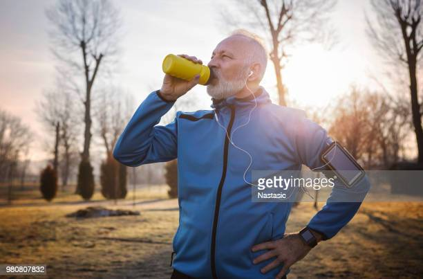 senior man hydrating - waist up stock pictures, royalty-free photos & images