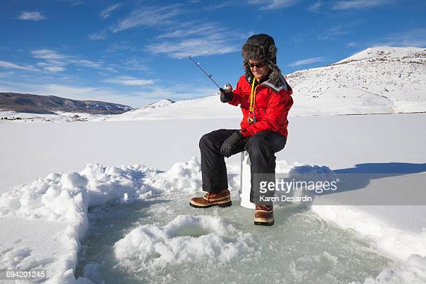 Senior man ice fishing for trout