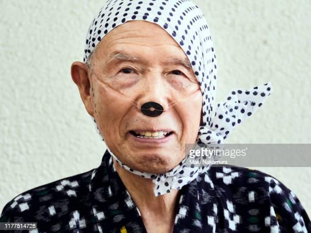 senior man imitating where he is taking a loach - 手ぬぐい ストックフォトと画像