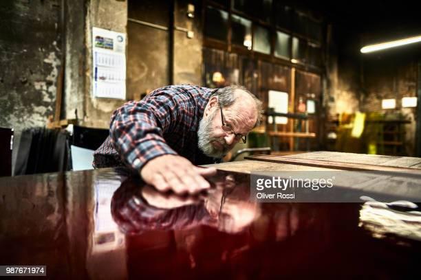 senior man in a glass factory examining glass pane - kunsthandwerker stock-fotos und bilder