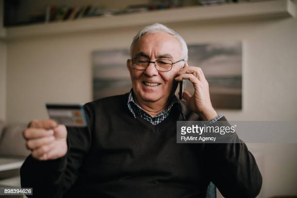 A senior man in a living room talking on a phone and reading his credit card number