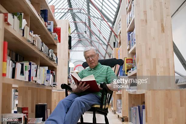 senior man in a rocking chair reading a book - einzelner senior stock-fotos und bilder