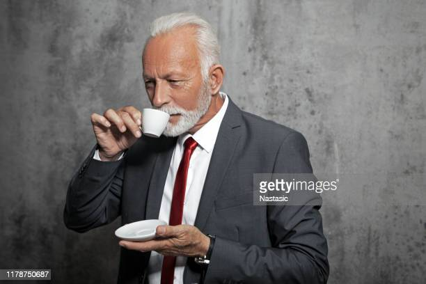 senior man in a suit drinking coffee - charming stock pictures, royalty-free photos & images