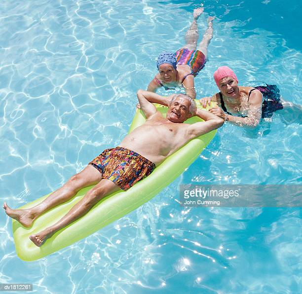 senior man in a swimming pool lying on an airbed which is being gripped by two senior women - man met een groep vrouwen stockfoto's en -beelden