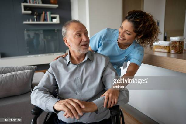 senior man in a wheelchair talking to his home caregiver - home caregiver stock pictures, royalty-free photos & images