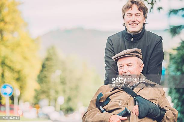 senior man in a wheelchair with his grandson, europe - carers stock photos and pictures