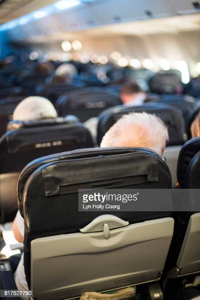 senior man in airplane seat - lyn holly coorg stock pictures, royalty-free photos & images