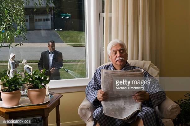 Senior man in armchair, reading newspaper, butler watering garden outside window