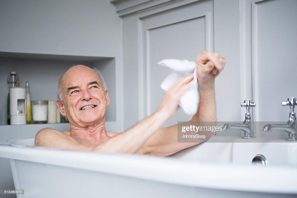 Senior man in bath washing himself smiling : Stock Photo