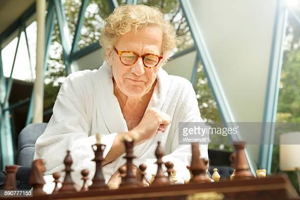 Senior man in bathrobe playing chess