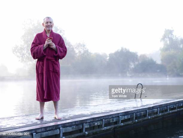 Senior man in bathrobe standing on jetty, portrait
