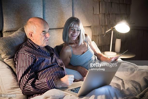 Senior man in bed wearing pyjamas with laptop