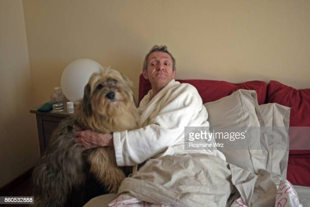 senior man in bed with his dog - hairy old man stock pictures, royalty-free photos & images