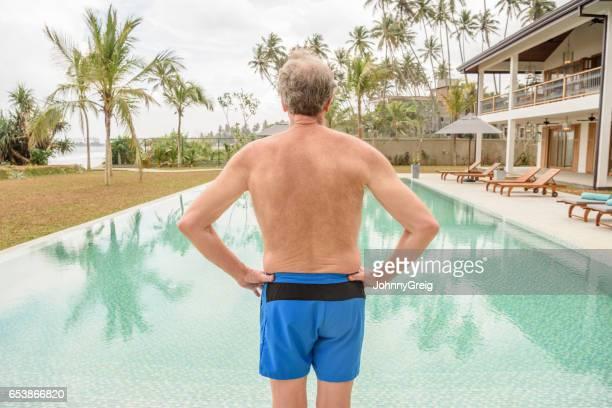 プールサイドでは、青色のトランクスで年配の男性背面図