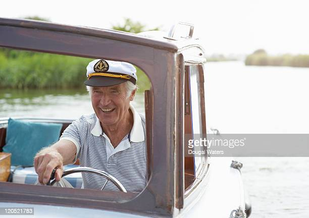 Senior man in boat wearing captain hat.
