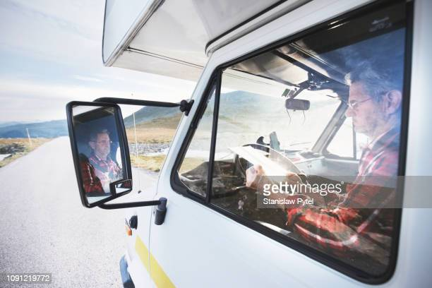 Senior man in campervan looking at map on road in mountains