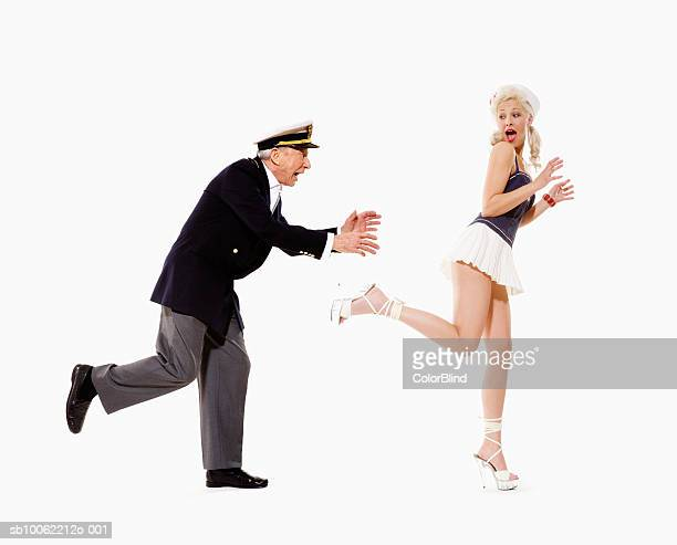 senior man in captain's jacket and hat chasing young woman in sailor swimsuit - may december romance stock photos and pictures