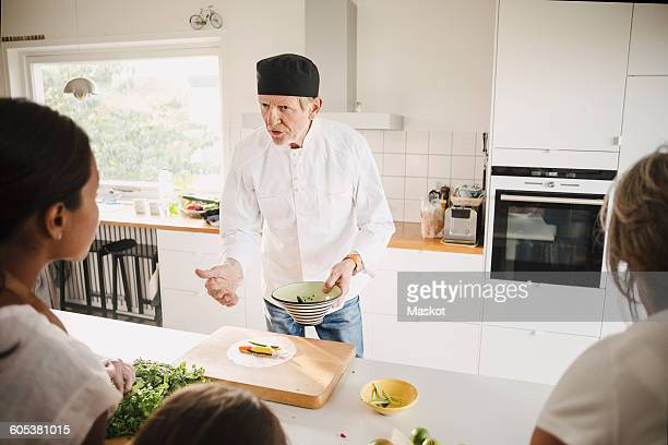 Senior man in chefs jacket talking to family while preparing food in kitchen