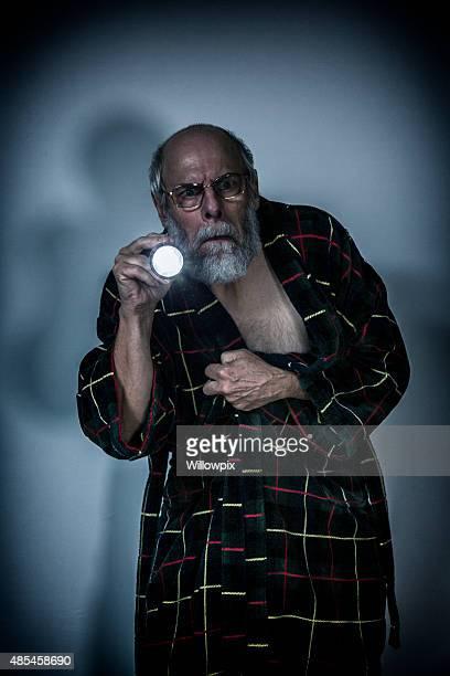 Senior Man in Dark Room Aiming Flashlight