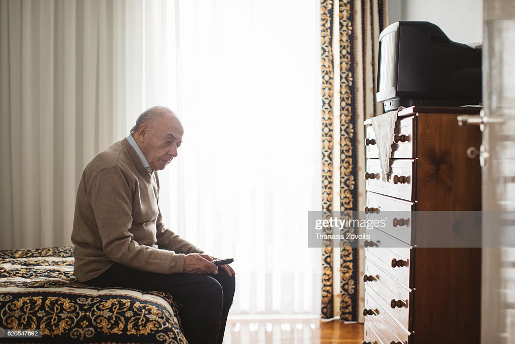 Senior man in front of a television : Stock Photo