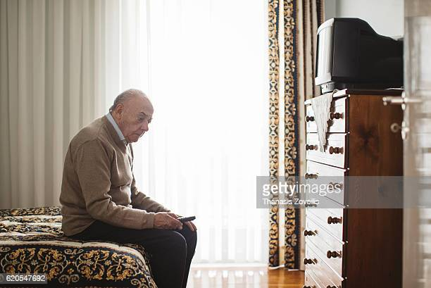 Senior man in front of a television