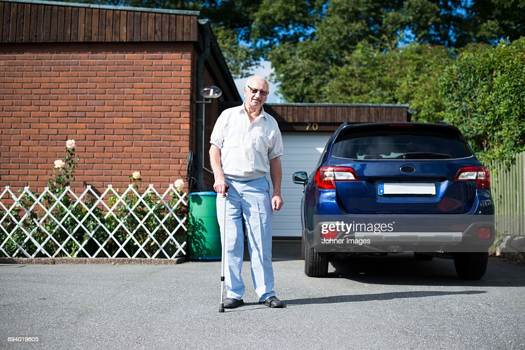 Senior man in front of car : Stock Photo