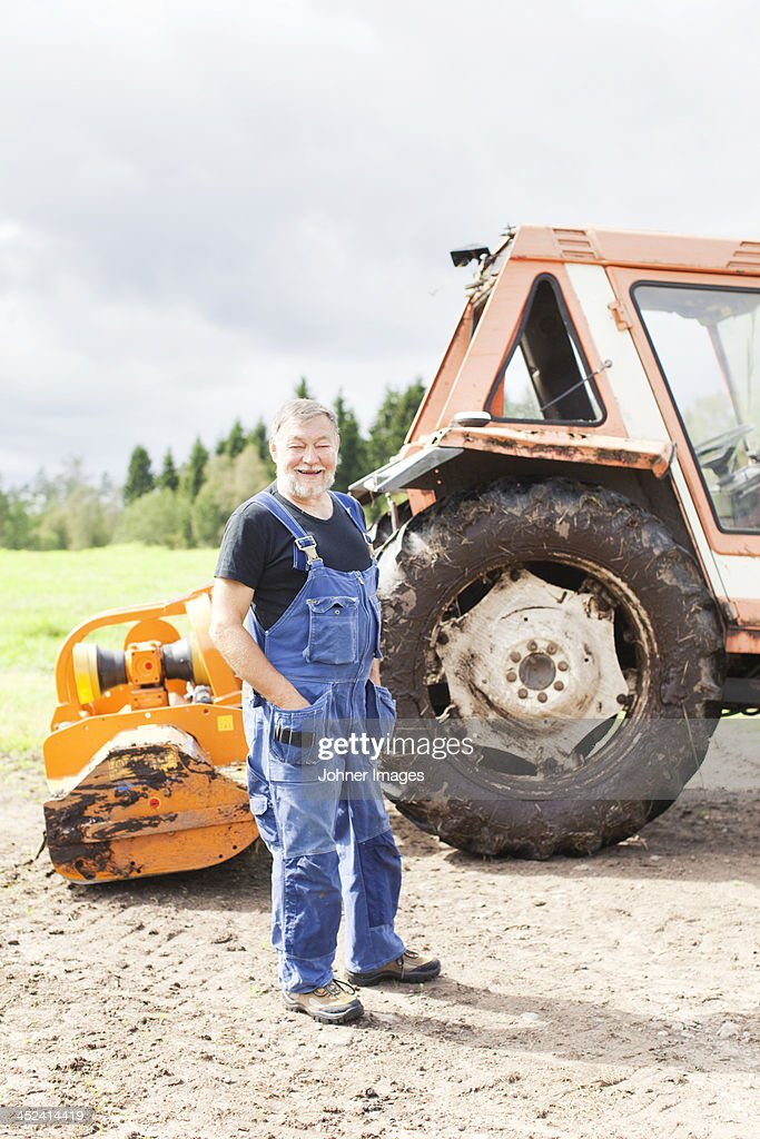 Senior man in front of tractor, Smaland, Sweden : ストックフォト