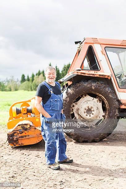 senior man in front of tractor, smaland, sweden - カバーオール ストックフォトと画像