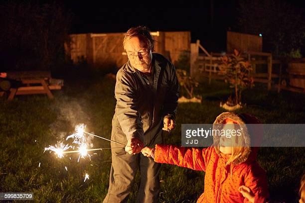 Senior man in garden handing sparkler to girl