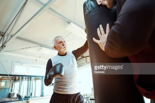 senior man in gym boksen met trainer - slaan met vuist stockfoto's en -beelden