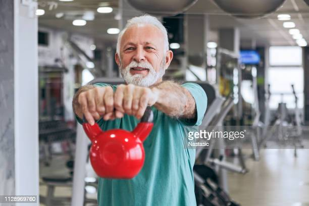 senior man in gym using kettle bells - sports training stock pictures, royalty-free photos & images