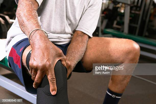 Senior man in gym wearing knee strap, holding knee, close-up