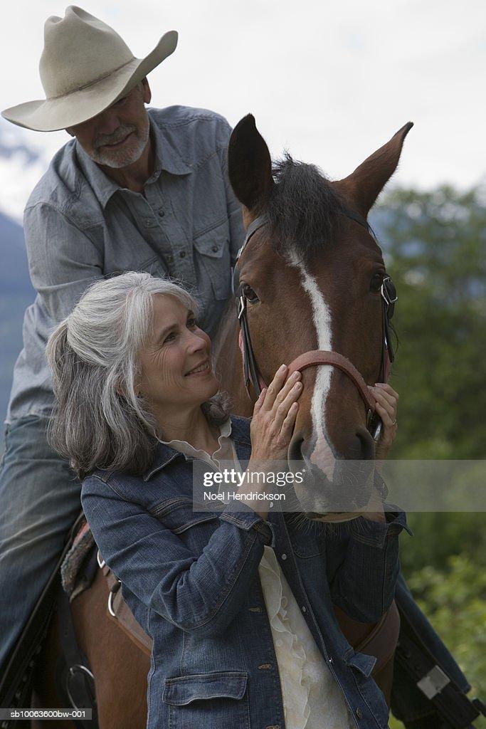 f16028f57 Senior Man In Hat Sitting On Horse Woman Stroking Animal Smiling ...