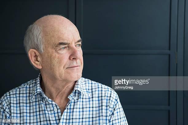 Alter Mann in seinem 70er Wegsehen gegen grauen Hintergrund