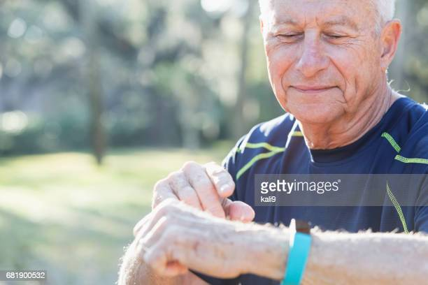 senior man in his 70s using fitness tracker - fitness tracker stock pictures, royalty-free photos & images
