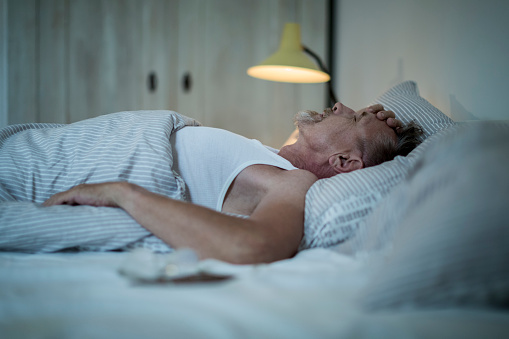 Senior man in his early 60s with greying beard is sick and sleepless in bed while night. - gettyimageskorea