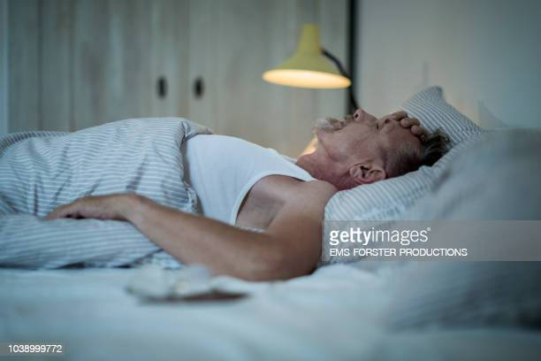 senior man in his early 60s with greying beard is sick and sleepless in bed while night. - grief fotografías e imágenes de stock