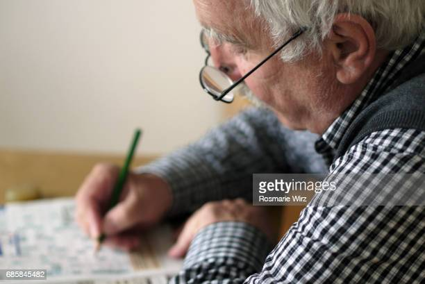 Senior man in his seventies doing crossword puzzle