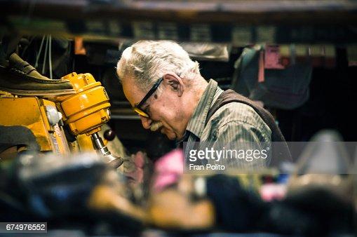 Senior man in his shoe repair shop.