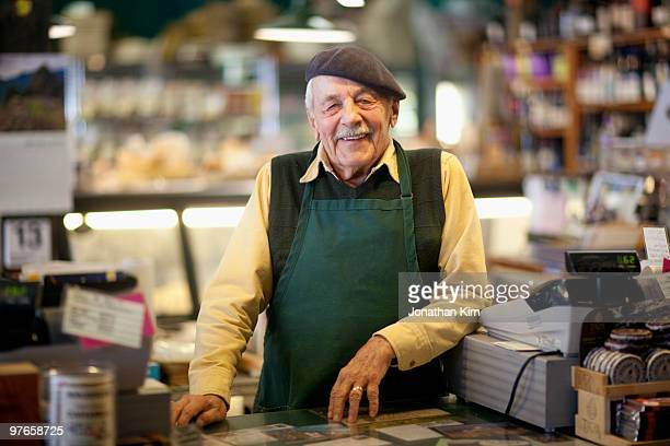 Senior man in his wine and cheese retail shop.