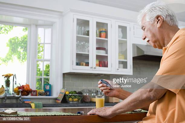 Senior man in kitchen, checking blood sugar levels