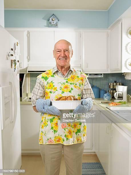 Senior man in kitchen,  holding dish with roasted chicken