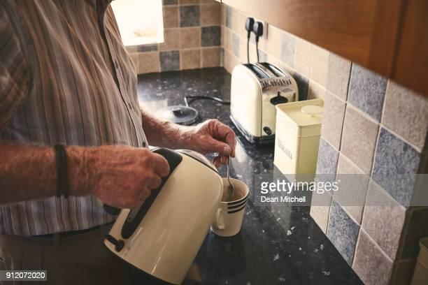 Senior man in kitchen preparing coffee